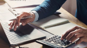 Homem fazendo conta na calculadora e usando computador