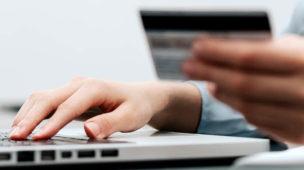 mulher segurando cartão de crédito e usando computador